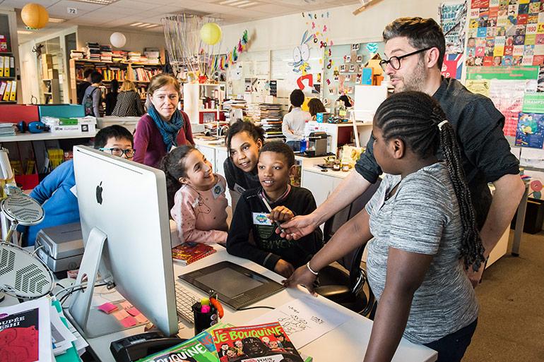 Locaux Montrouge Bayard Jeunesse - le directeur artistique du plateau lecture explique son métier à des enfants visiteurs