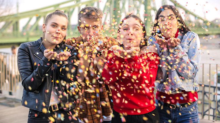 © AdobeStock - Adolescents soufflants des confetti